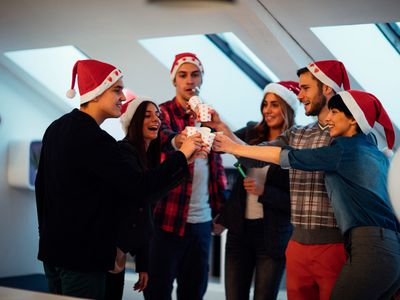 Group of coworkers toasting each other and drinking at an office holiday party.