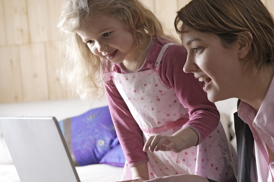 Mother and daughter (3-5) using laptop computer, smiling