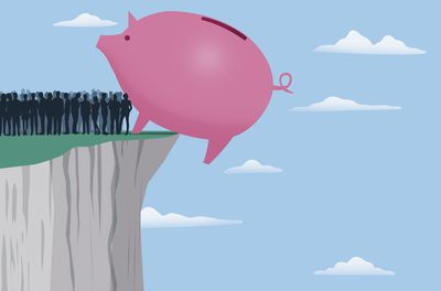 Crowd of people standing next to huge piggy bank balanced on edge of cliff