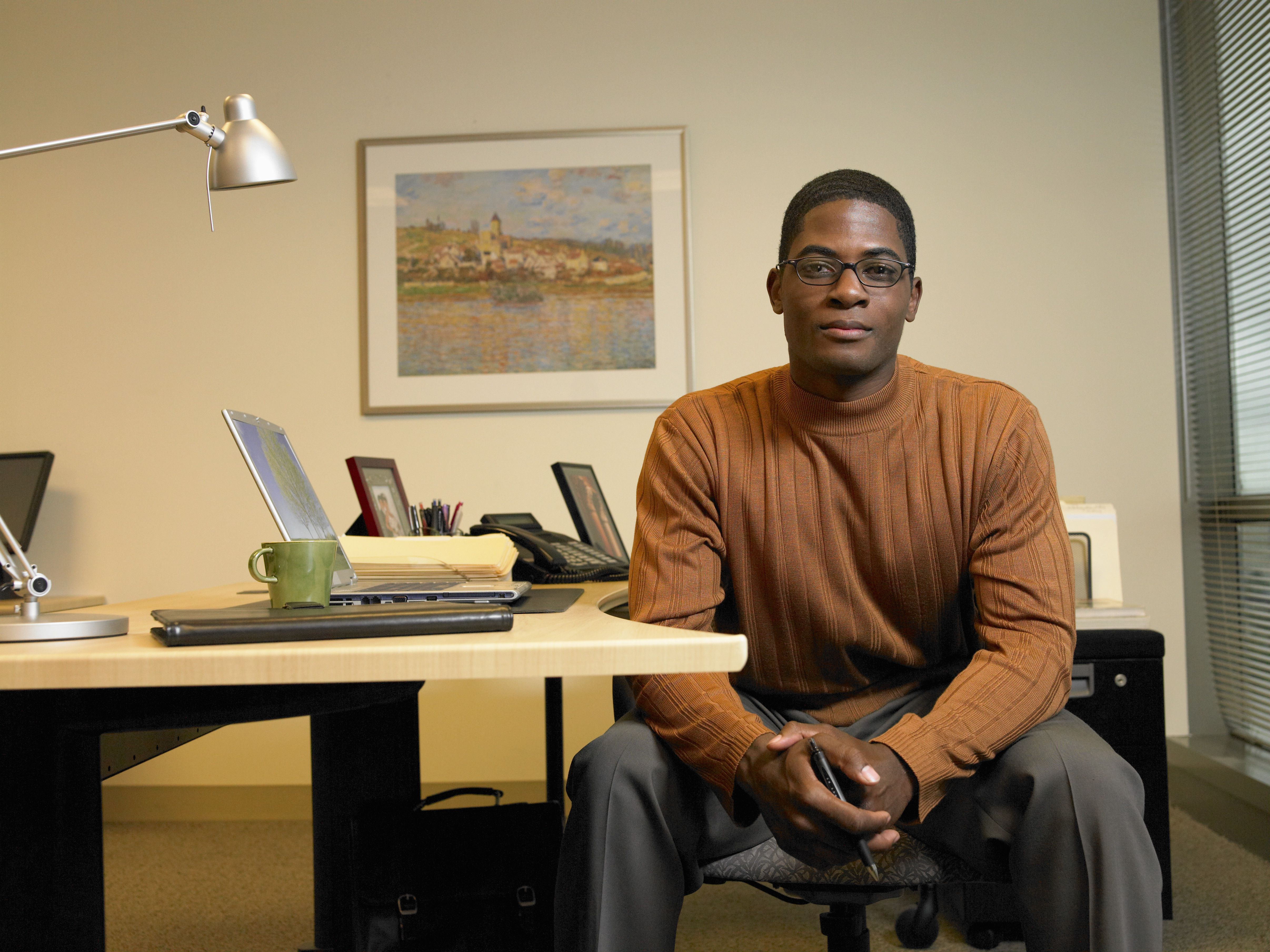 Man dressed in a stylish sweater and nice pants at his desk