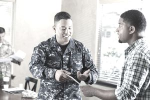 Soldier talking to young man at military recruitment event
