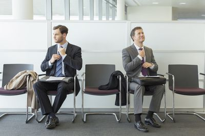 Applicants in a waiting area getting ready for an interview by straightening their ties.