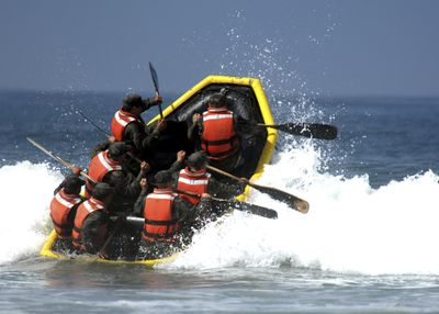 Basic Underwater Demolition/SEAL students battle through the surf during their last day of Hell Week.