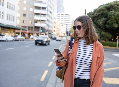 Woman on a city street uses a crowdsourced app.