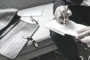 Close-up of businessman writing and drawing in notebook