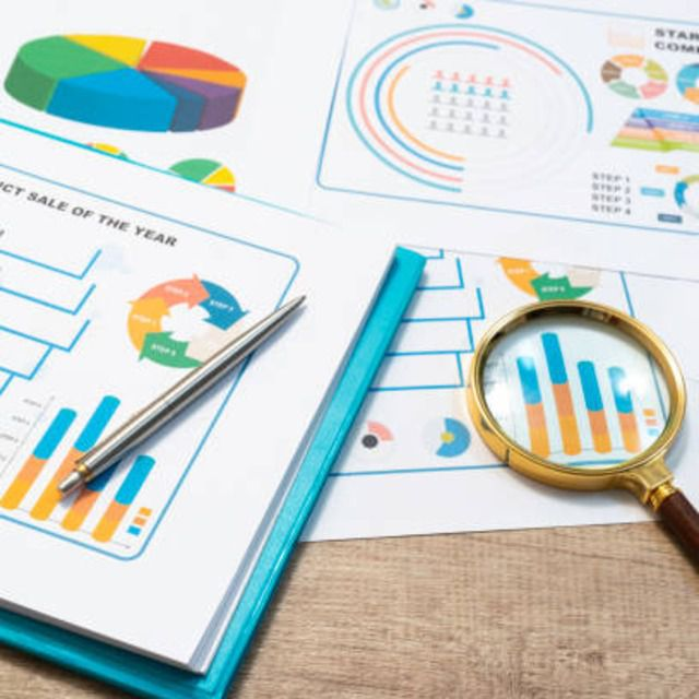 Magnifying glass and pen laying atop documents of analytics data of industry trends