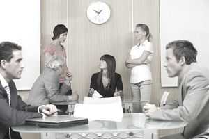 Group of businesspeople communicating with strained looks on their faces