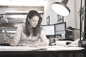 Woman working at her desk, developing a strategy to manage change in a project.