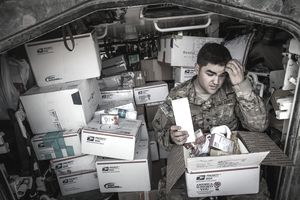 A soldiery opens a gift package, sent to him in the mail.