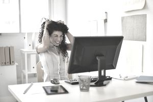 Woman sitting at work in front of her computer grabbing her hair in anger