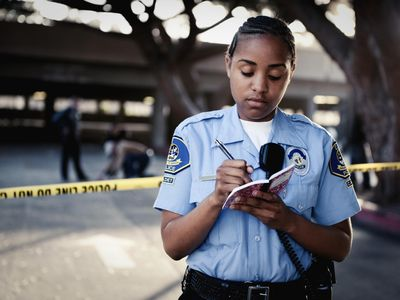 African American policewoman writing in notebook
