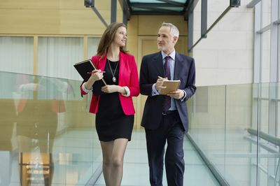 two business people walking down a cooridor