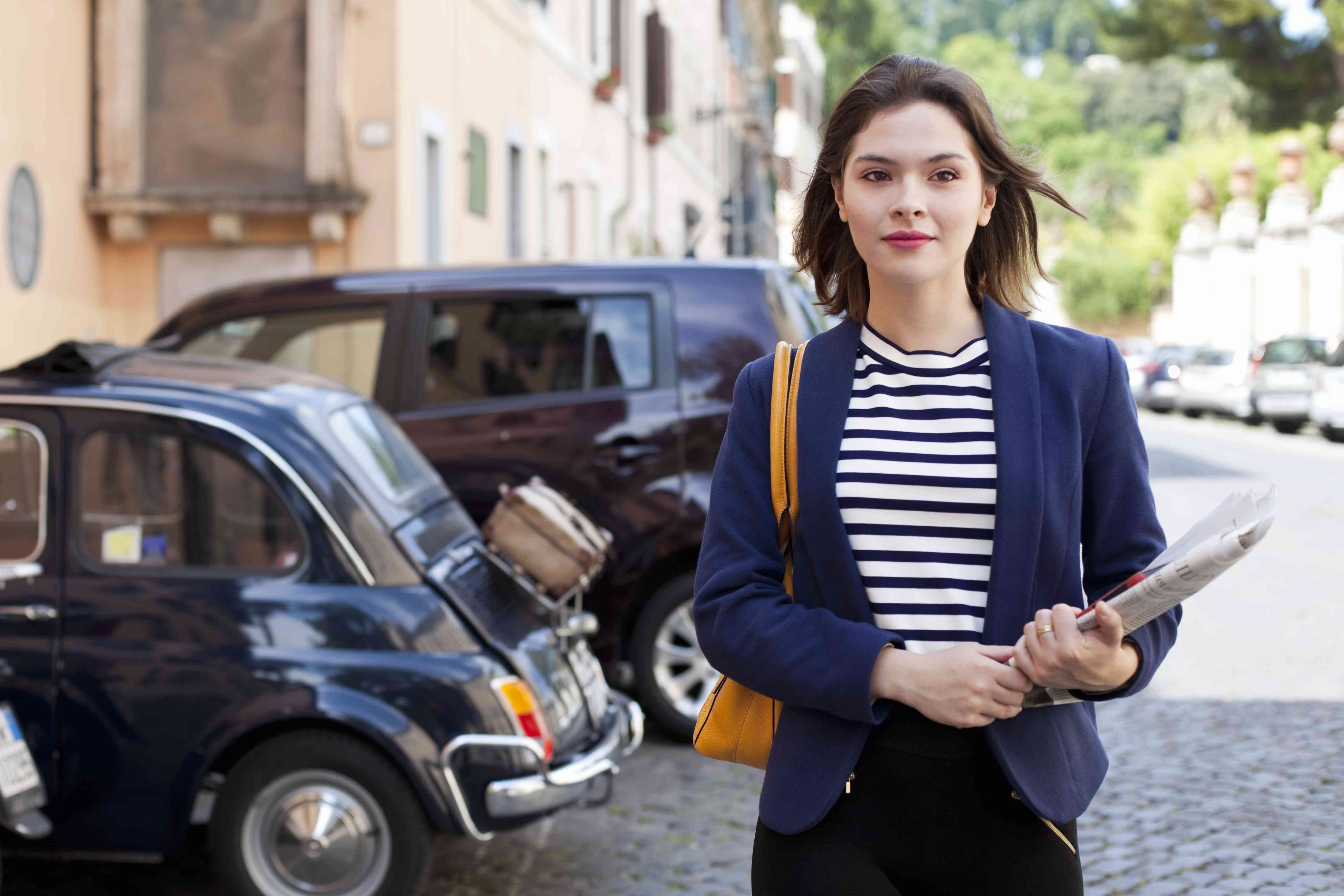 young business woman walking down the street carrying a newspaper