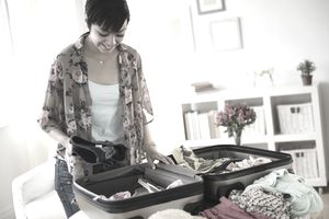 Woman packing a suitcase with a smile
