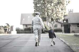 Rear view of female soldier walking with son at military air force base