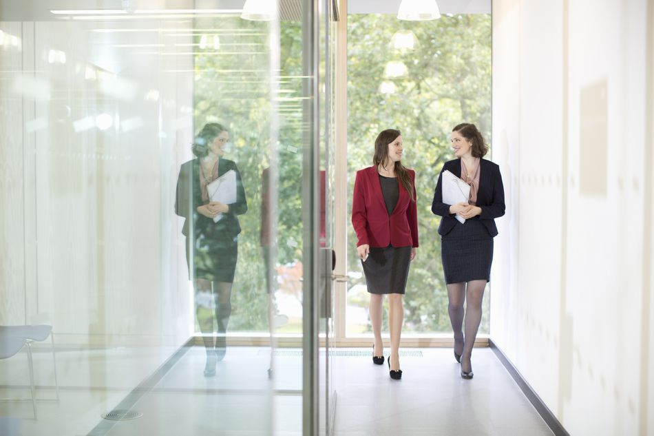 Businesswomen walking in modern office hallway