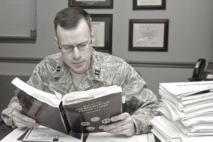 Military member reading Manual for Courts-Martial