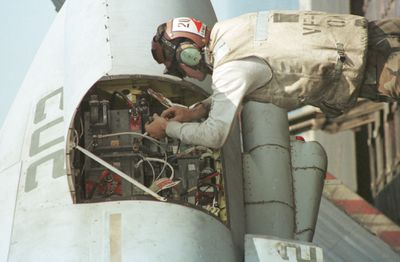 Flight crew technician working on the electronics of an F-14 fighter jet aboard the carrier USS Enterprise somewhere in the Arabian Sea prior to a strike mission in Afghanistan.