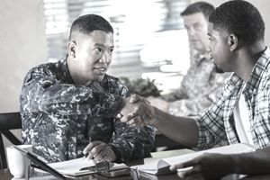 Military recruiter meeting with young man at military recruitment event