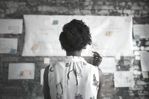 businesswoman looking at a flow chart on the wall of her office by herself.