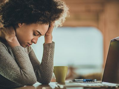 African American woman having a headache from working on a computer at home.
