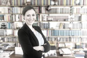 Smiling literary agent standing in front of a bookcase and piles of books