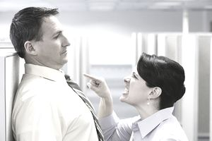 Female office worker castigating male office worker between cubicles