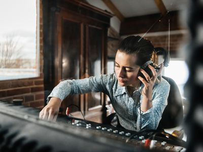 Female sound engineer in a recording studio paid for with a business funding loan.