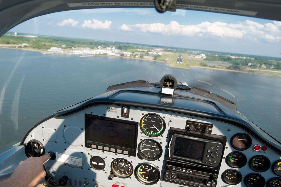 Cockpit and dials of a small plane in flight as it comes in for a landing