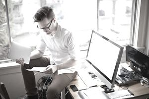 Freelancer sitting on desk reviewing paperwork and holding tablet.