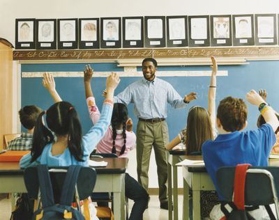Teacher standing in front of a class of students raising hands
