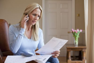 Concerned woman holding bills and talking on cell phone