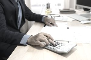 Tax examiner working at office desk using a calculator to verify numbers