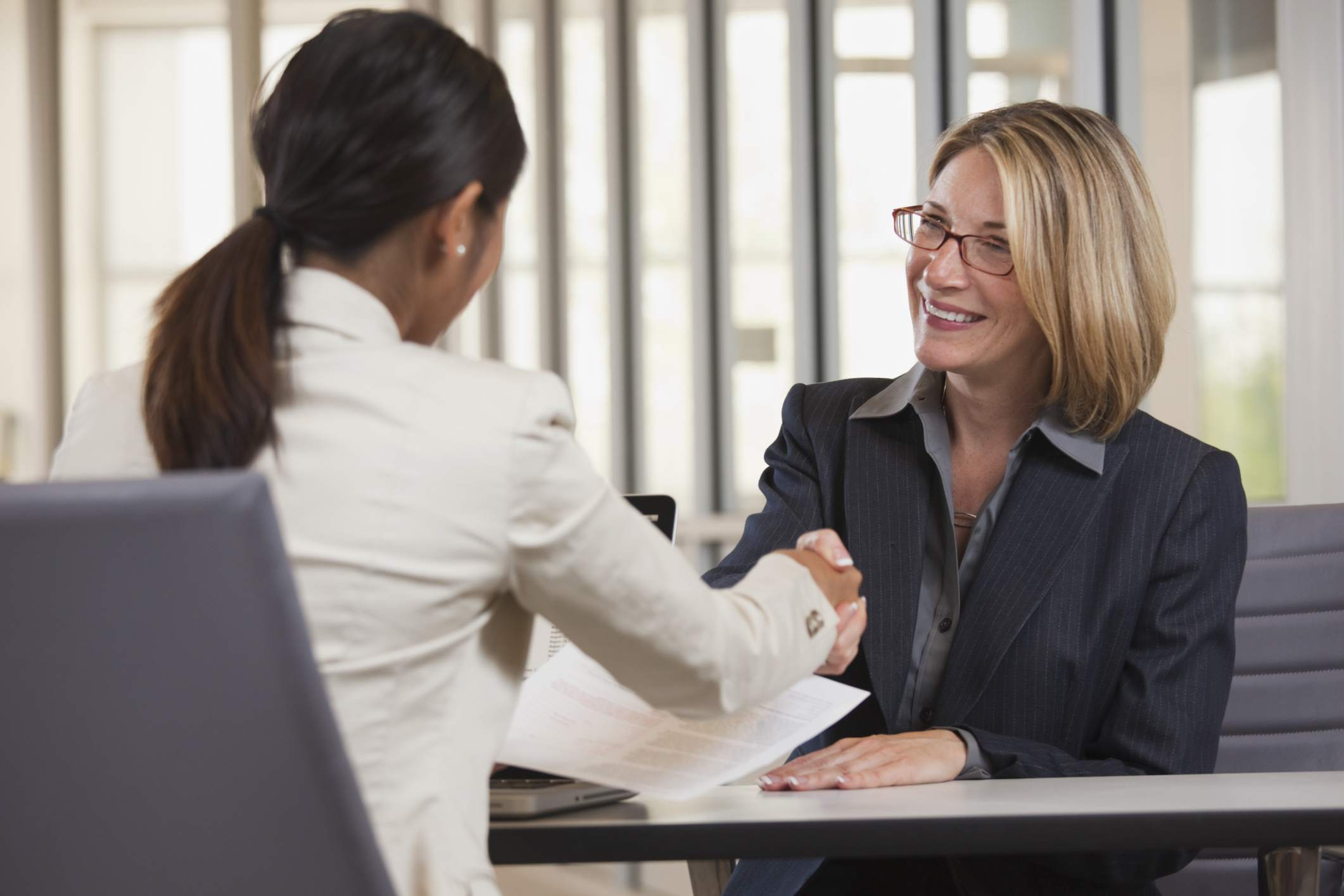 A formal recognition and thank you letter and a congratulatory handshake are exchanged by to female employees.