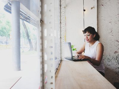 Woman working on a laptop by a cafe window