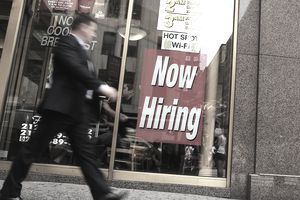Man walks past now hiring sign