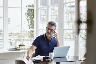 Businessman using mobile phone while writing notes