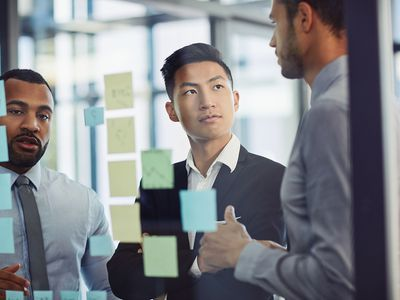 Employees brainstorming together with ideas on sticky notes
