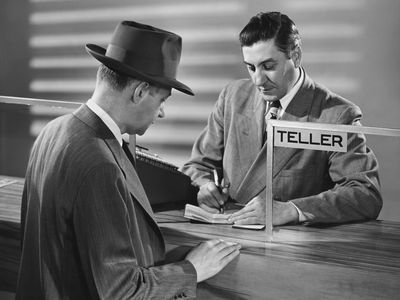 Mature man standing in front of a bank teller in a bank