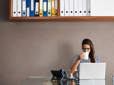 Personal assistant sitting at desk drinking coffee and looking at a laptop
