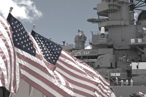 US Flags Beside Battleship Missouri Memorial with Four Sailors