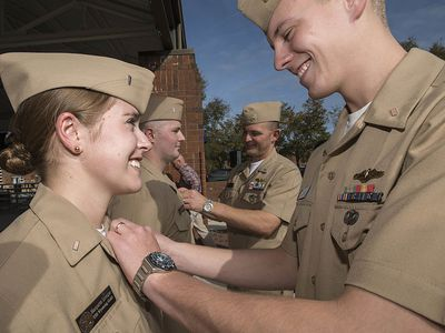 Man putting pin on woman in the navy