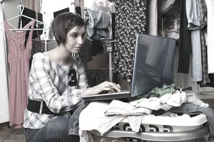 woman on laptop with clothes