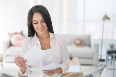 Woman at home reading a new employee welcome letter from her new employer.