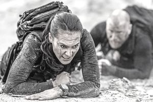 Male and female military duo crawling together during operations in muddy sand