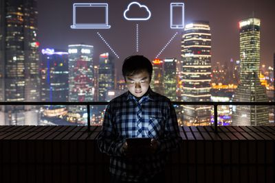Person using a table on a balcony studying an information library with thought bubbles of cloud technology