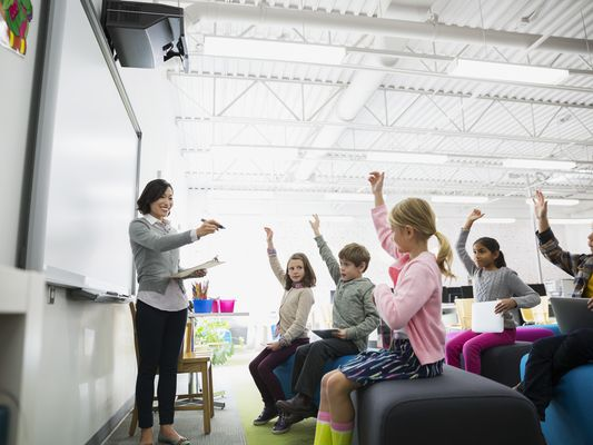 Teacher pointing to students with arms raised