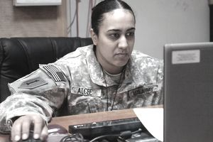 a female soldier working in front of a computer