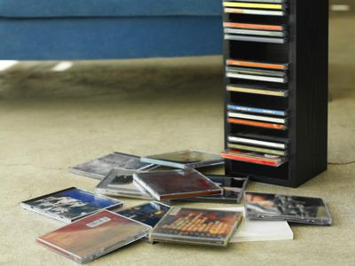 Cd storage unit with cds on the floor and sofa in the background