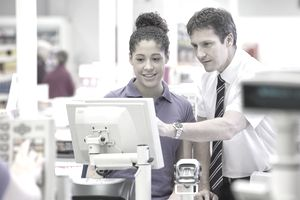 Supermarket manager training a young cashier